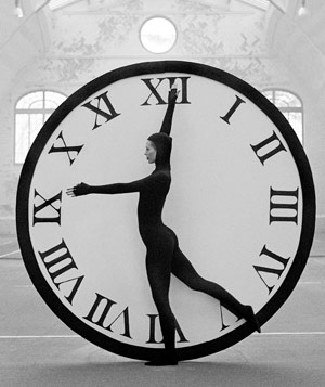 Black and white photograph of woman in catsuit in front of giant clock