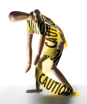Wooden human figure model wrapped in yellow caution tape