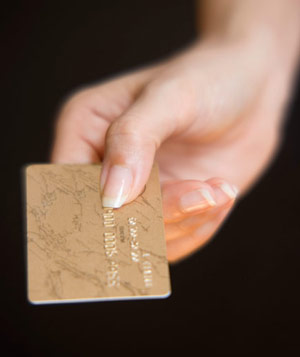 Woman's hand holding gold credit card