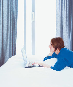 Woman on laptop in hotel room