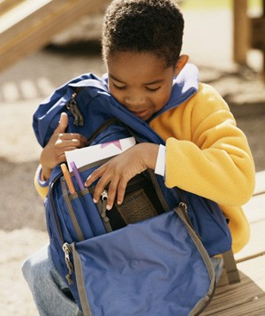 Child looking inside blue backpack