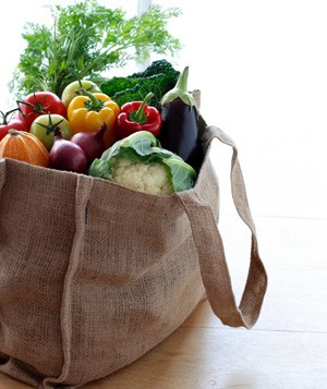 Canvas shopping bag filled with vegetables on table