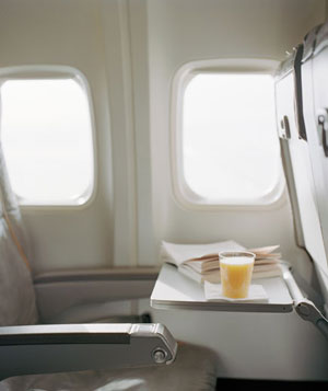Orange juice and book on open airplane tray