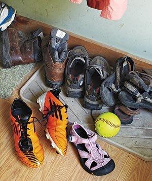 Shoes scattered throughout messy mudroom