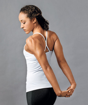 Woman stretching her arms behind her back