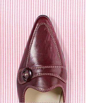 Scratched shoe on pink striped background
