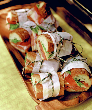 Sandwiches on a wooden platter tied with twine