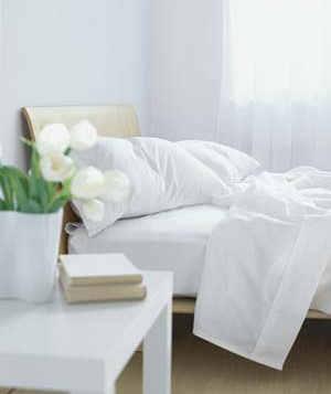 Nightstand and bed with white sheets