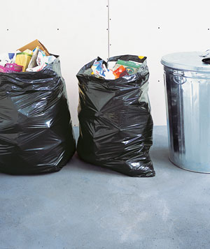 Two garbage bags next to a garbage can