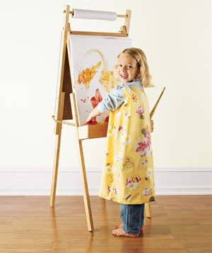 Child wearing pillowcase smock and painting