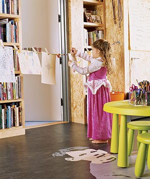 Child hangs her artwork on a clothesline