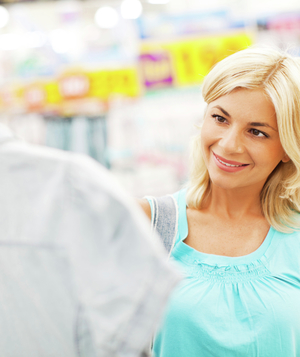 Woman holding up shirt in store