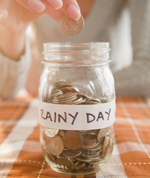 Saving coins in  rainy day  jar