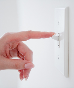 Hand turning off a light switch