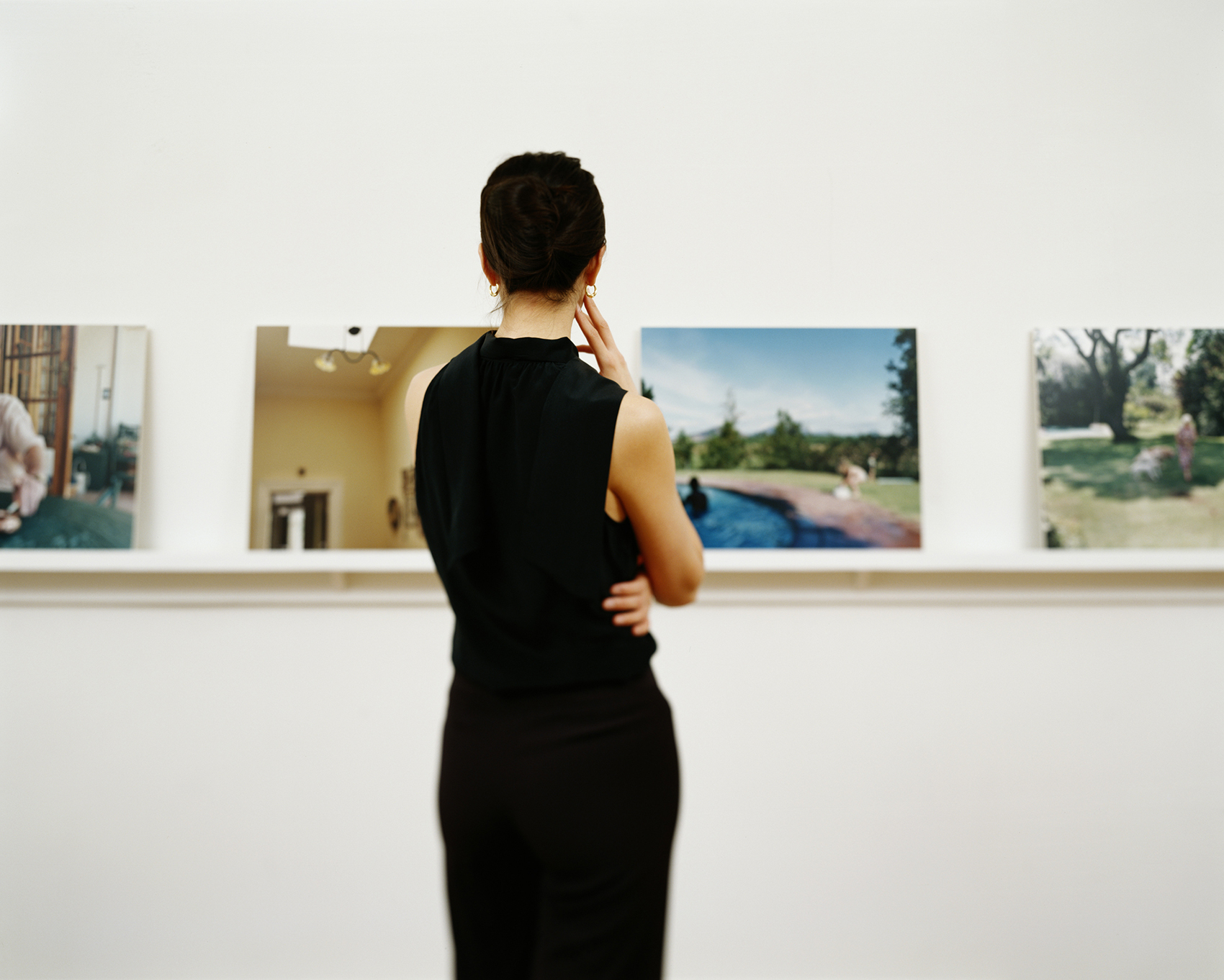 Woman staring at photos in art gallery