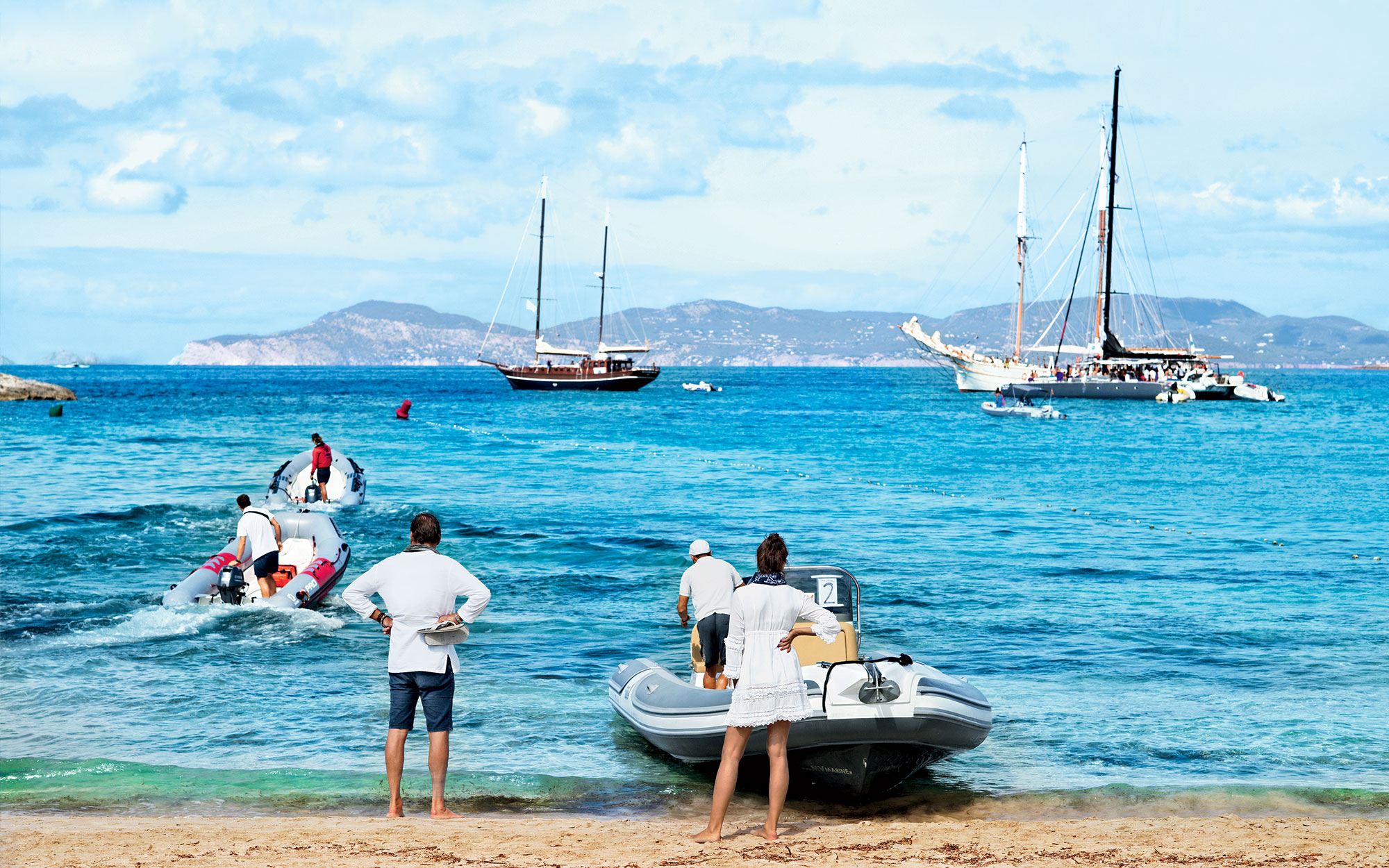 Boats are taking guests from boats to shore (and back) in front of the restaurant Juan y Andrea on Platja IlletesFormentera, Spain09/2015