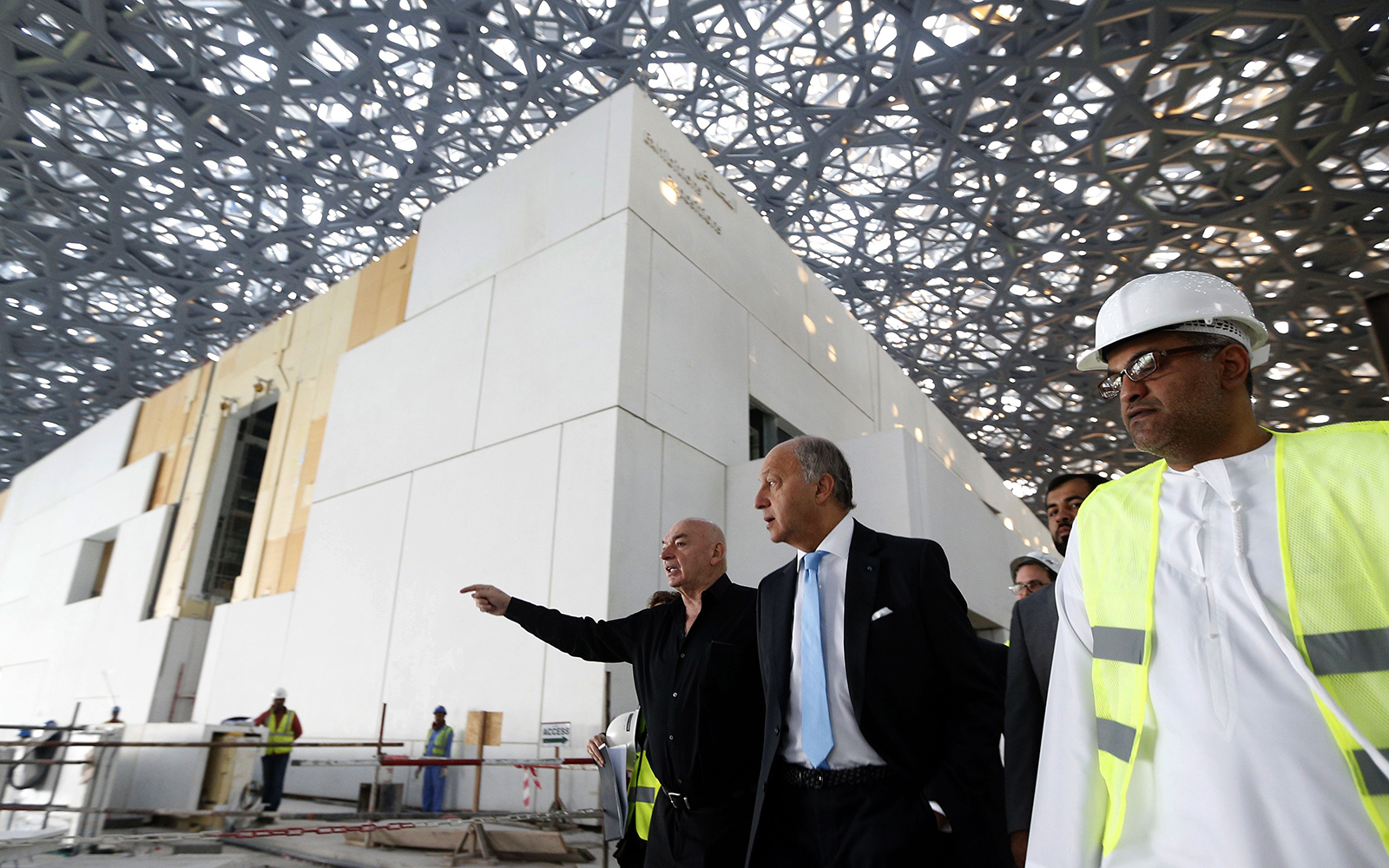 French Foreign Minister Laurent Fabius (C) and French architect Jean Nouvel (L) visit the construction site of the future Louvre museum on Saadiyat island, outside the UAE capital Abu Dhabi on January 18, 2016.Fabius visits UAE to attend the 9th edition