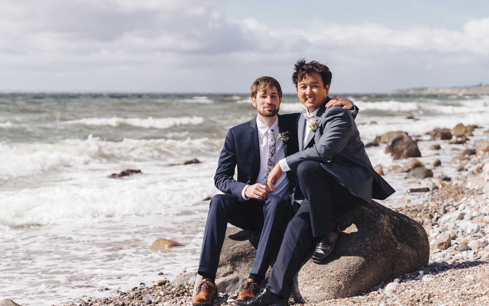 Newlyweds sit together on beach at the Baltic Sea