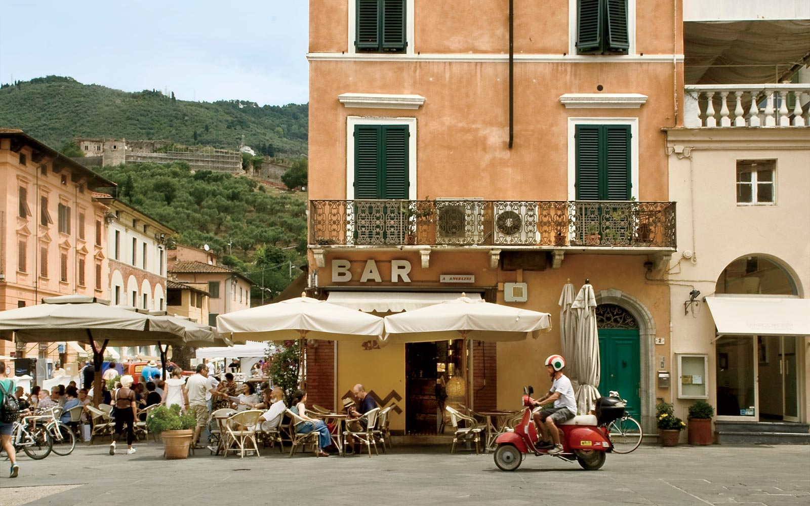 Riding a scooter through the town of Pietrasanta, in Tuscany, Italy