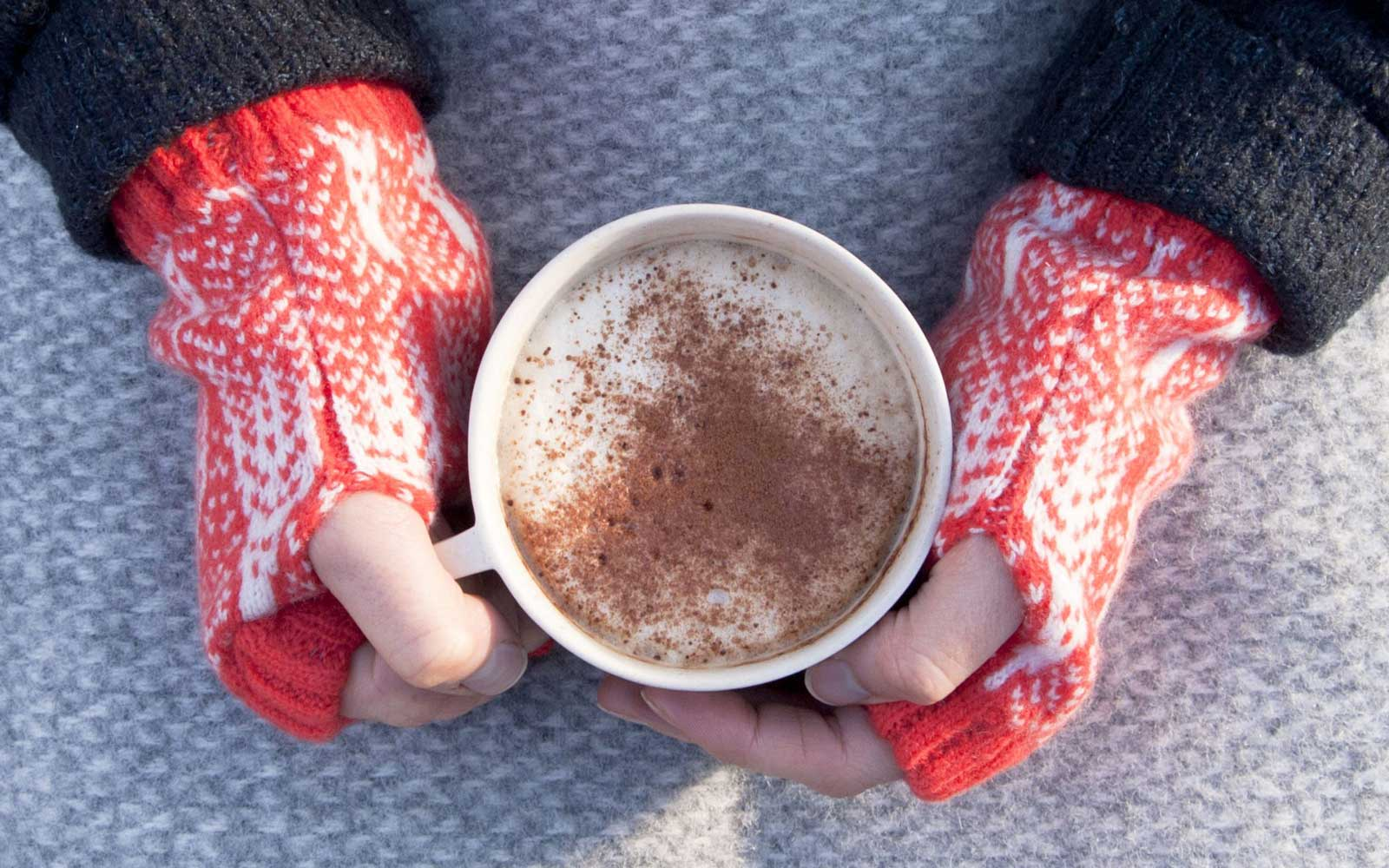 Hands with fingerless gloves wrapped around a cup of hot cocoa
