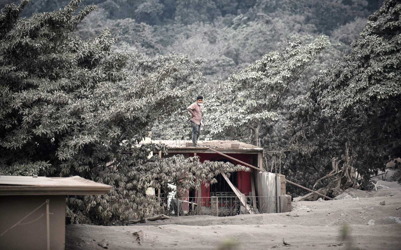 A man stands on the roof of a house in the ash-covered village of San Miguel Los Lotes, in Escuintla Department, about 35 km southwest of Guatemala City, taken on June 4, 2018, after the eruption of the Fuego Volcano.