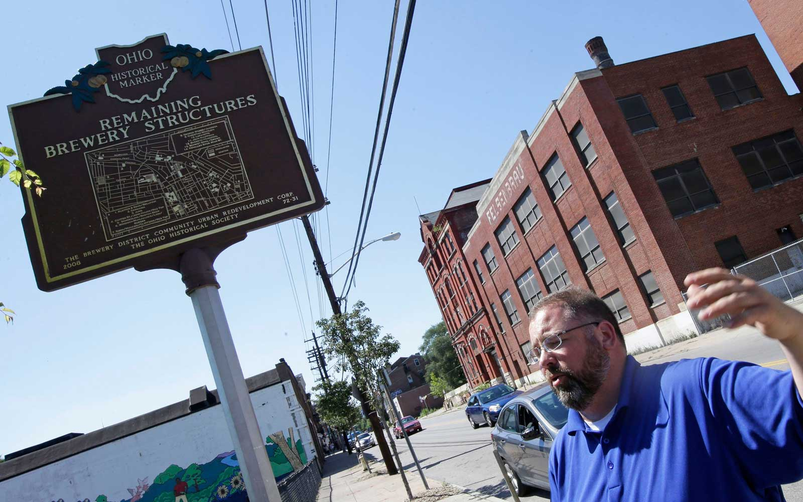 Steve Hampton, a local architect and the part-time executive director of the nonprofit Brewery District Community Urban Development Corp., stands near a sign showing the history of the brewery district, in Cincinnati.