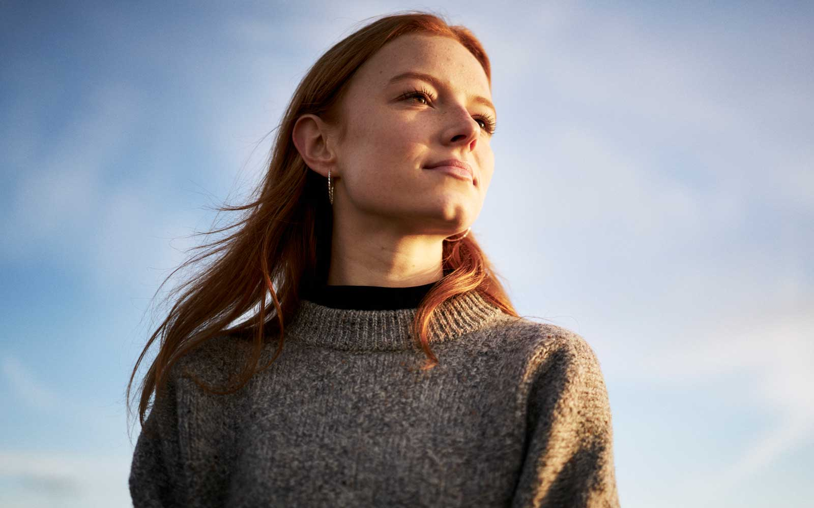Woman standing in the sunlight in winter