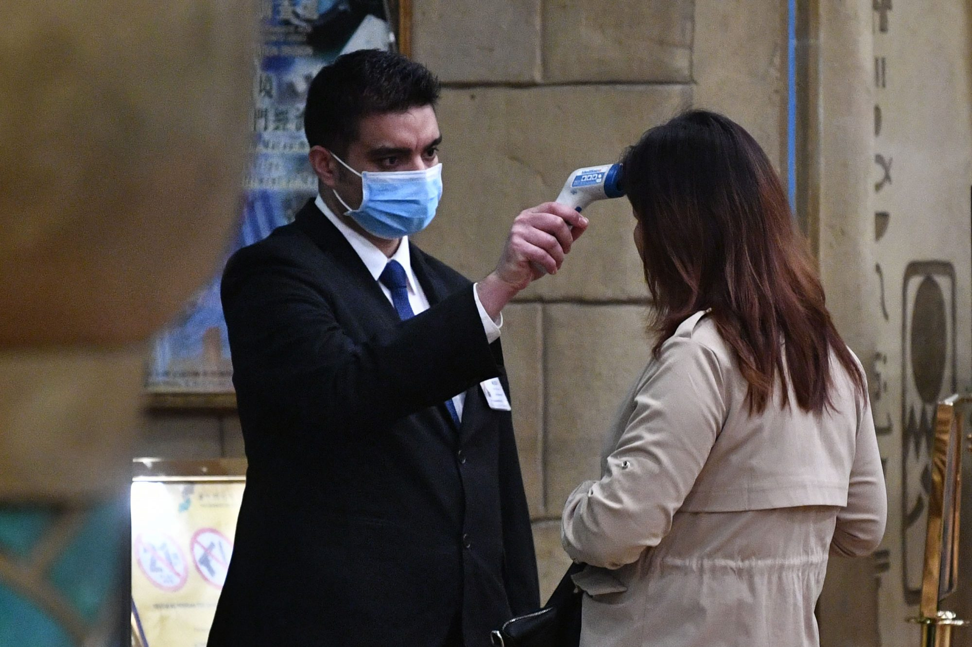 A staff member checks the temperature of a guest entering the casino of the New Orient Landmark hotel in Macau.