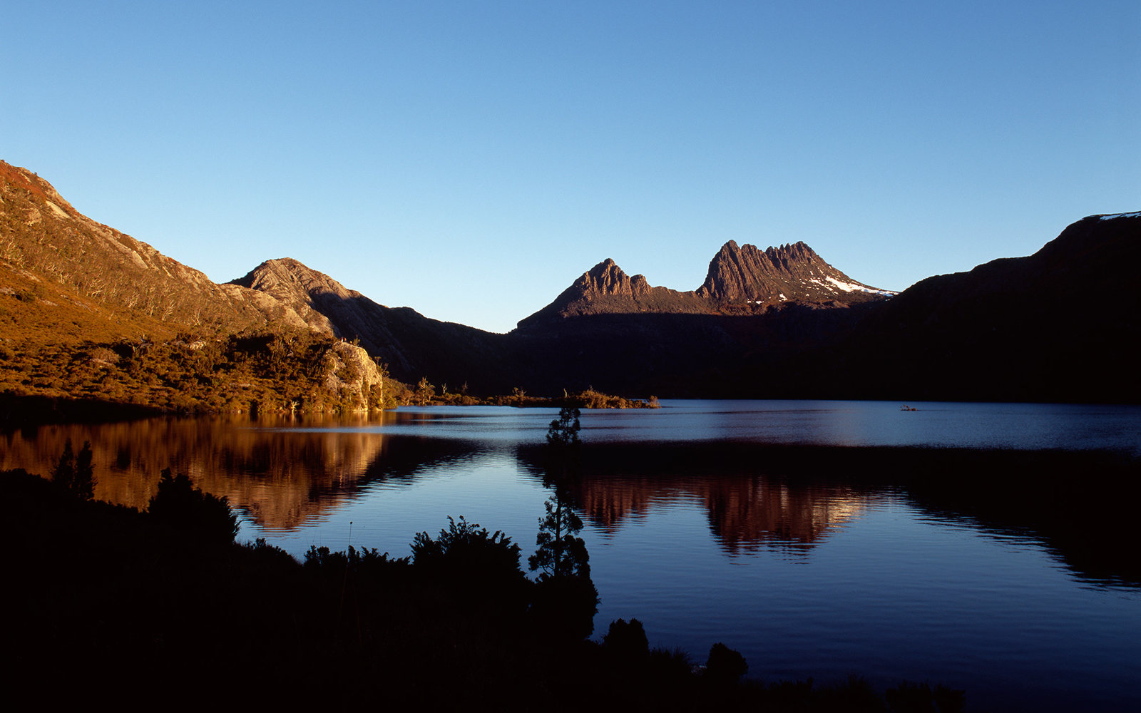 Ancient glacial crags reflected in the still waters of Dove Lake.
