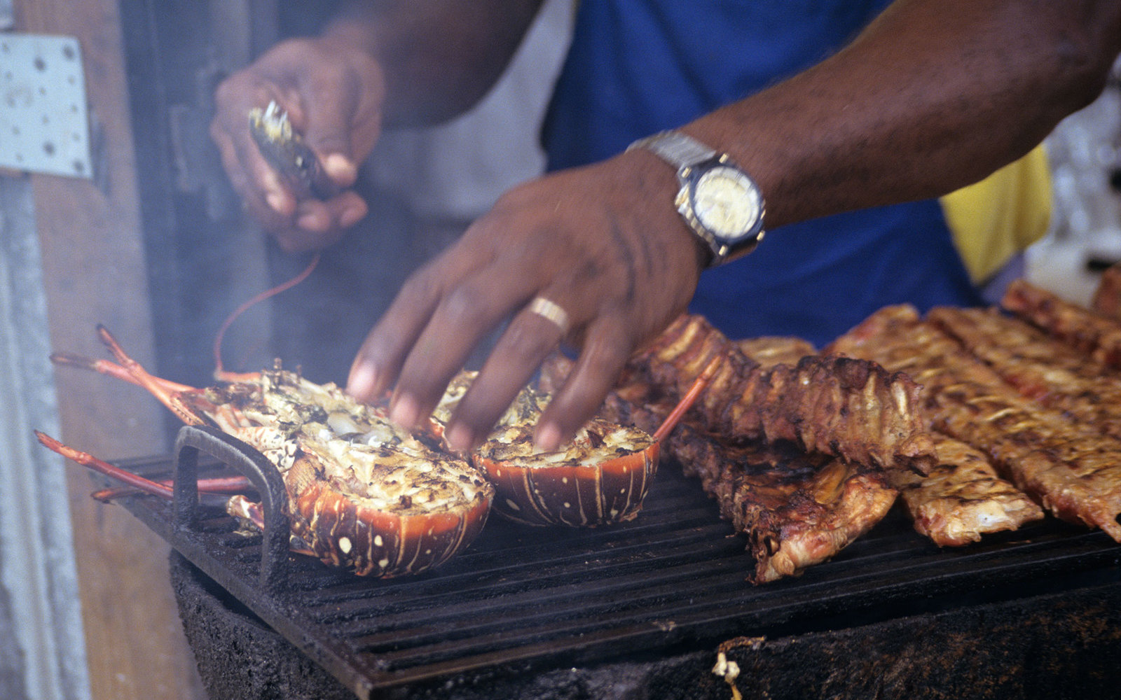 AKAYBB Lobster being cooked on a Barbecue with cooks arms and smoke in Anguilla Caribbean