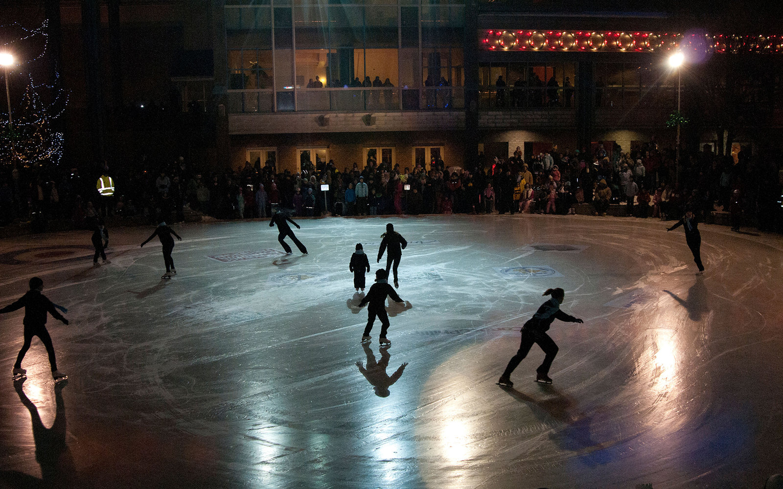 C53GEG Ice skaters perform for the public on New Year's Eve in Town Square Park, downtown Anchorage, Southcentral Alaska, Winter