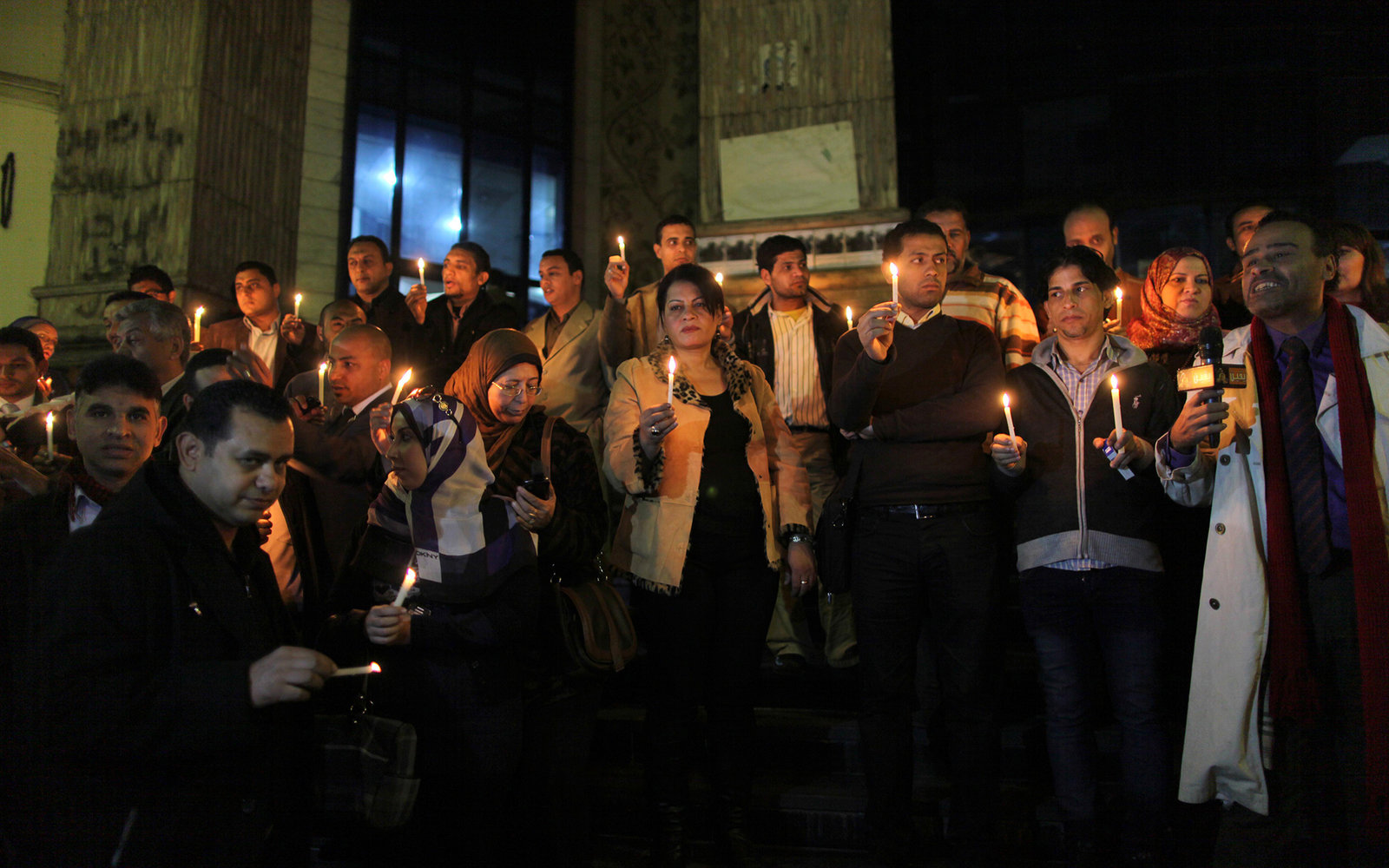 D1NDGG Dec. 31, 2012 - Cairo, Cairo, Egypt - Egyptian activists hold candles as they take part in a rally on the anniversary of the attack on the All Saints Church (al-Qiddissine) in the city of Alexandria two years ago, as the gather on new Year's eve in