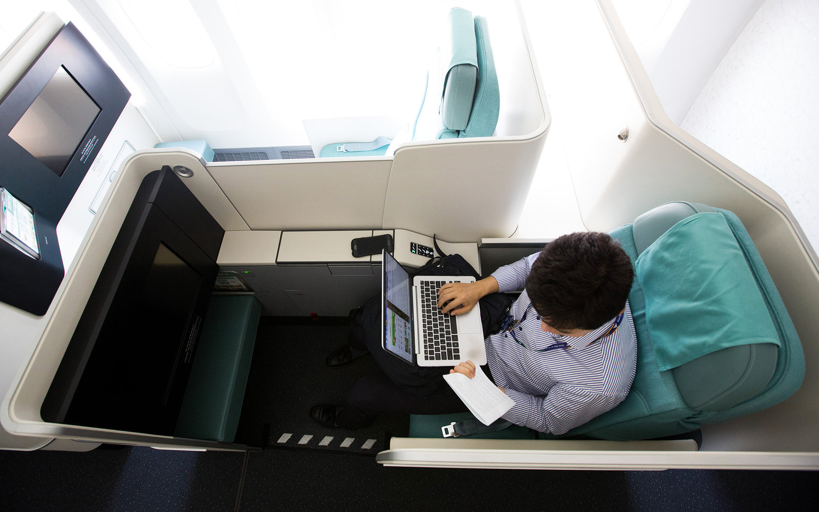 A member of the media uses his laptop computer inside a business class seat of a Korean Air Lines Co. Boeing Co. 747-8 passenger aircraft during a media preview at Incheon International Airport in Incheon, South Korea, on Tuesday, Sept. 1, 2015. Korean Ai