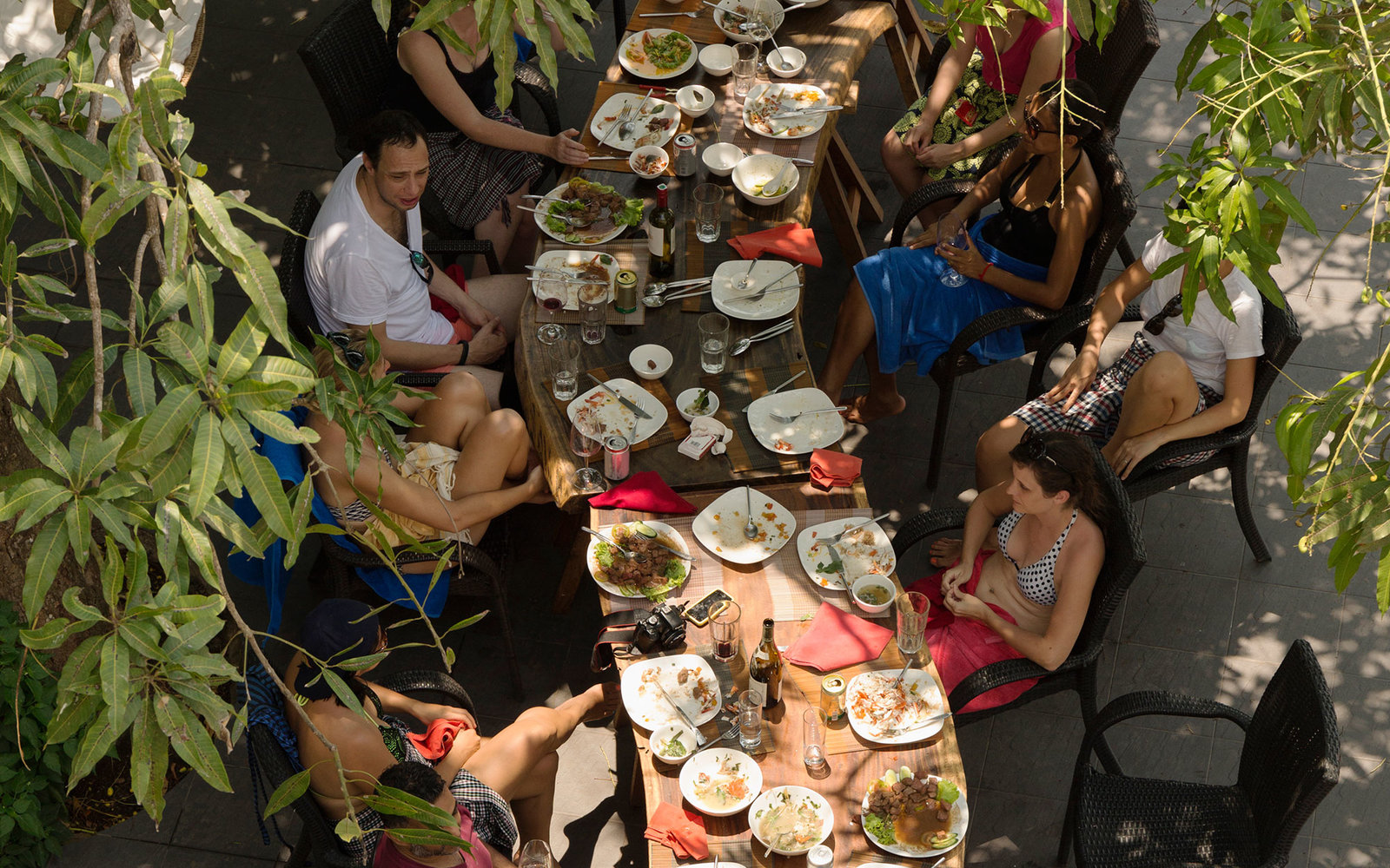 Overhead view of tourist friends having lunch at long table, Kep, Cambodia