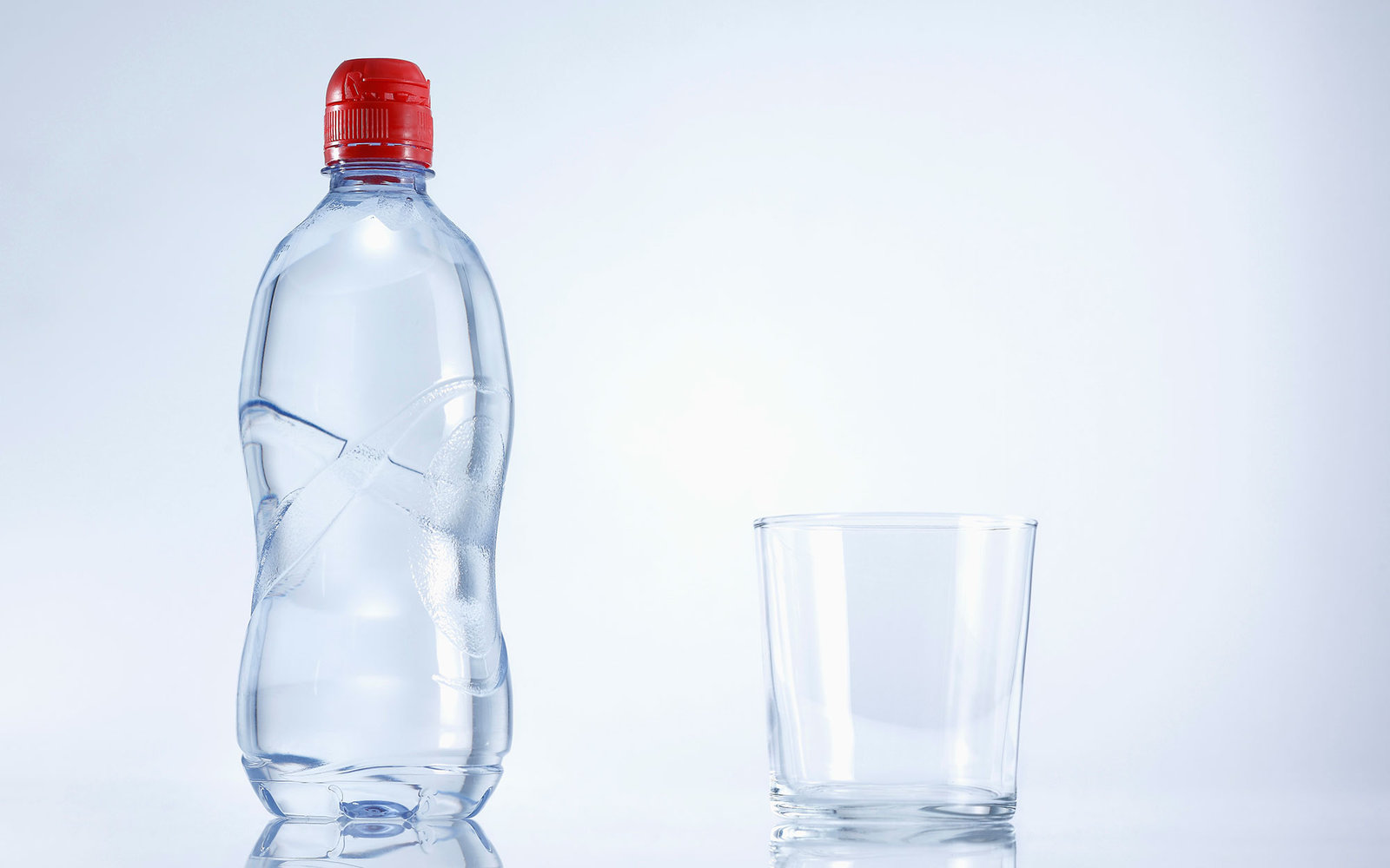 Plastic bottle of mineral water with glass, close up