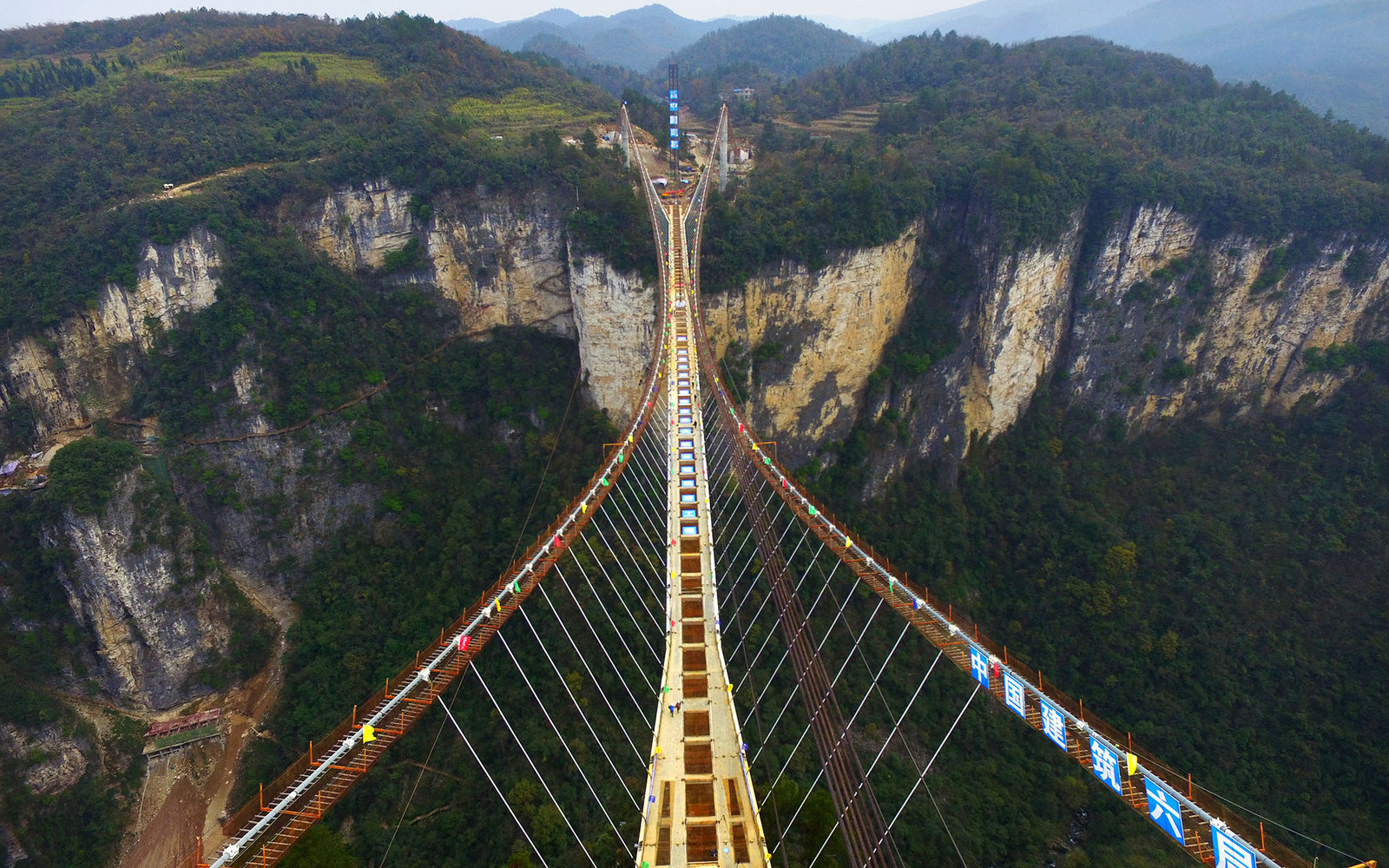 ZHANGJIAJIE, CHINA - DECEMBER 03:  (CHINA OUT) Aerial view of the glass-bottom bridge with steel beams completed at Tianmenshan National Forest Park on December 3, 2015 in Zhangjiajie, Hunan Province of China. World's longest glass-bottom bridge between t