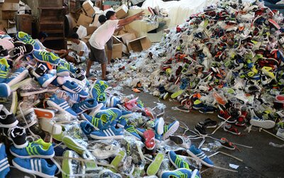 67563591fe7c Workers for the Philippine customs bureau pile up thousands of confiscated  counterfeit designer footwear products at