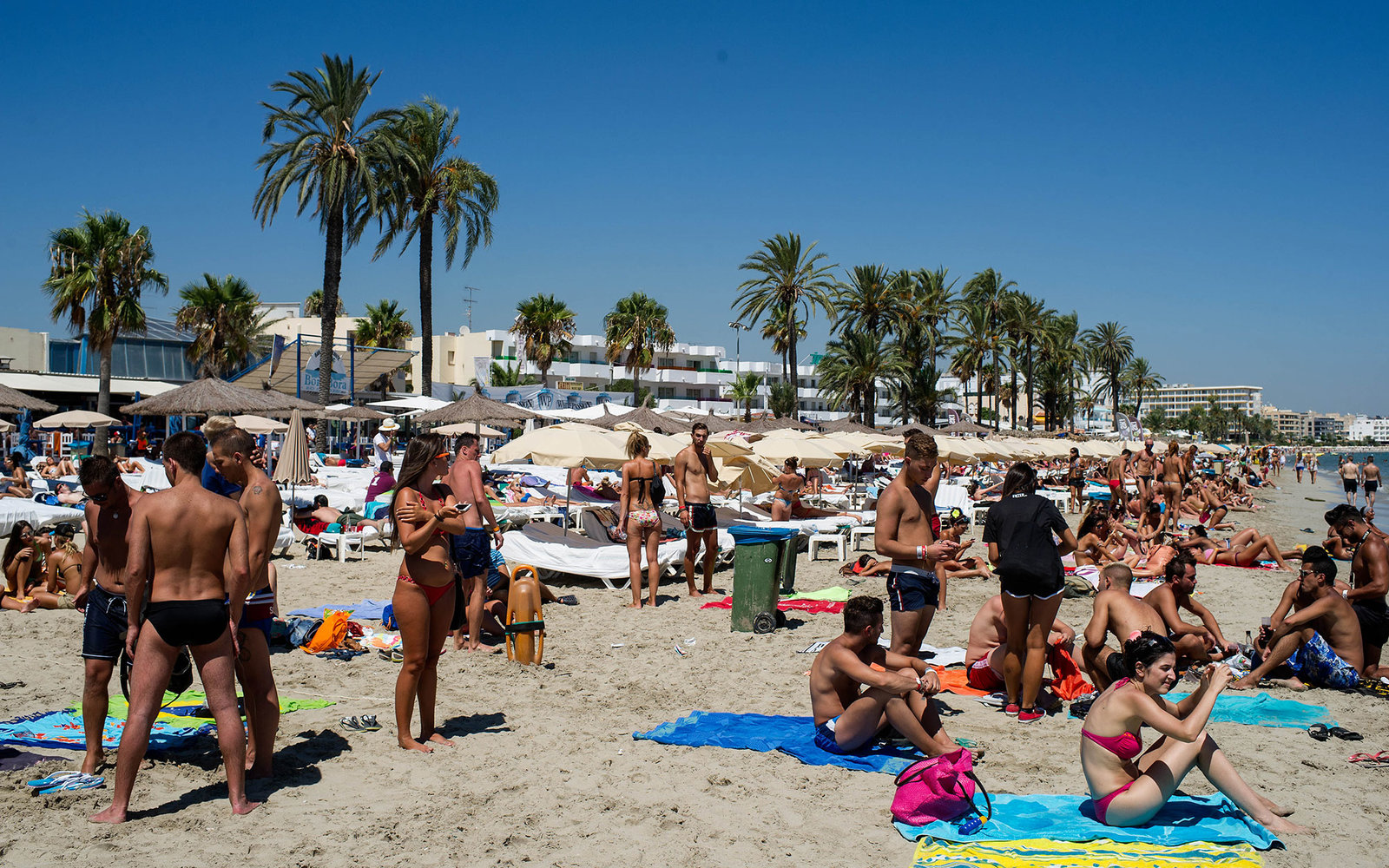 IBIZA, SPAIN - AUGUST 21:  People sunbathe at Platja d'en Bossa beach on August 21, 2013 in Ibiza, Spain. The small island of Ibiza lies within the Balearics islands, off the coast of Spain. For many years Ibiza has had a reputation as a party destination