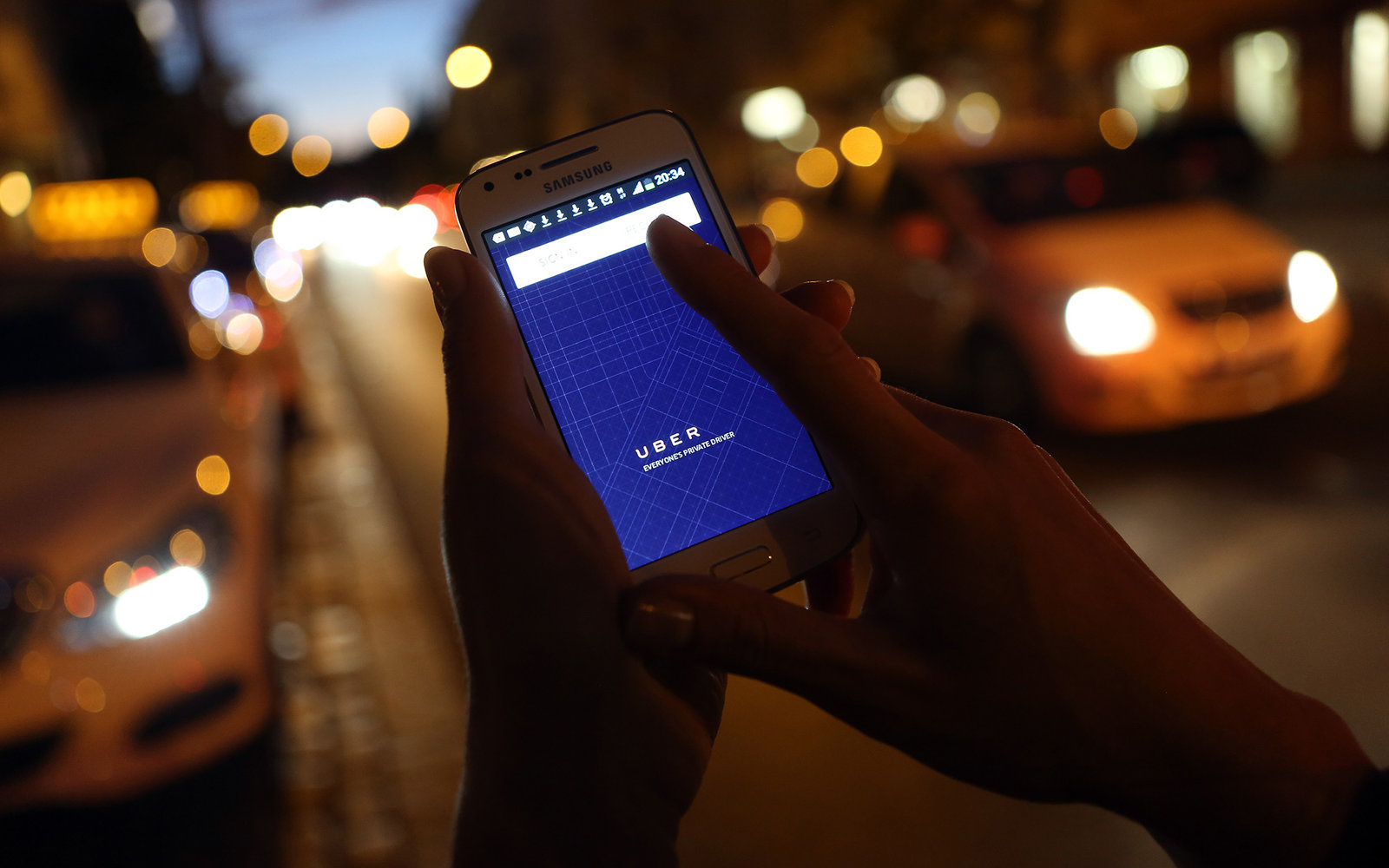 BERLIN, GERMANY - SEPTEMBER 02:  In this photo illustration, a woman uses the Uber app on an Samsung smartphone on September 2, 2014 in Berlin, Germany. Uber, an app that allows passenger to buy rides from drivers who do not have taxi permits, has had its