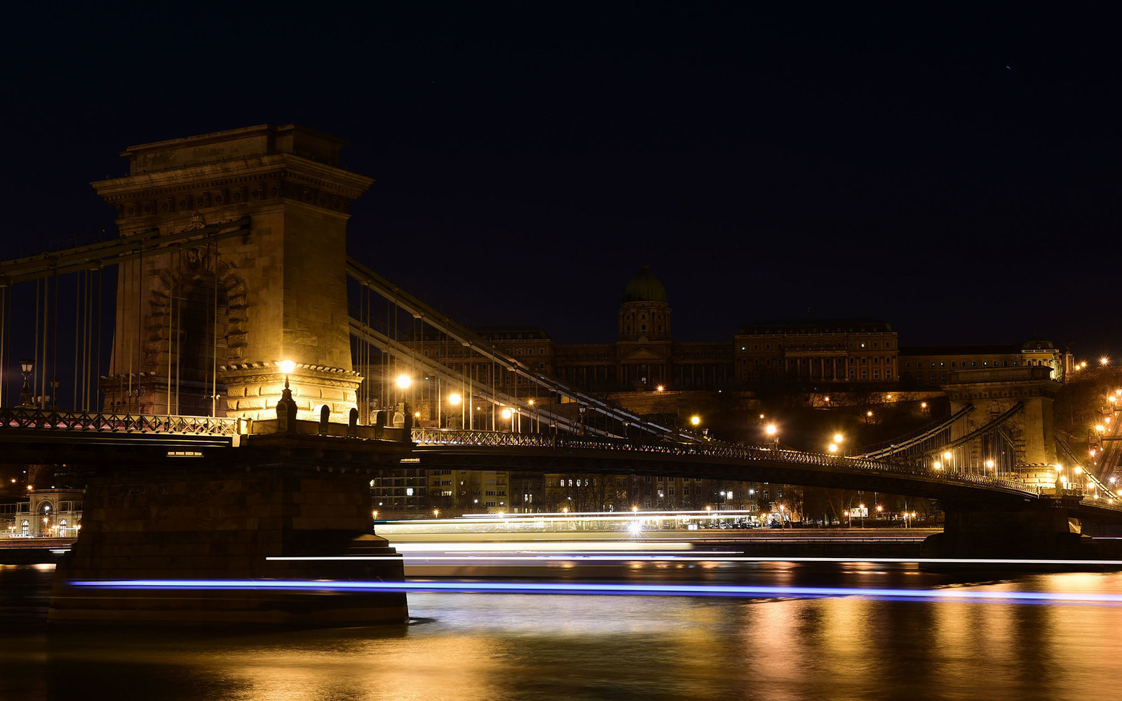 Picture taken on March 19, 2016 shows the oldest Hungarian bridge, the 'Chain Bridge' with the Buda Castle on top of the Castle Hill of Budapest downtown after the city lights were switched off to mark the annual Earth Hour event.Lights went off in thous