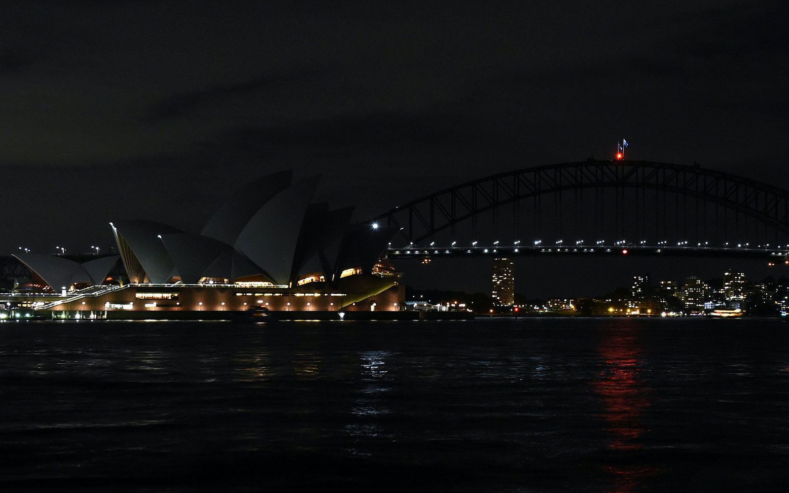 This picture taken on March 19, 2016 shows Australia's iconic Sydney Opera House and Harbour Bridge with the lights turned off during the Earth Hour campaign in Sydney.Millions of people from 178 countries and territories are expected to take part in