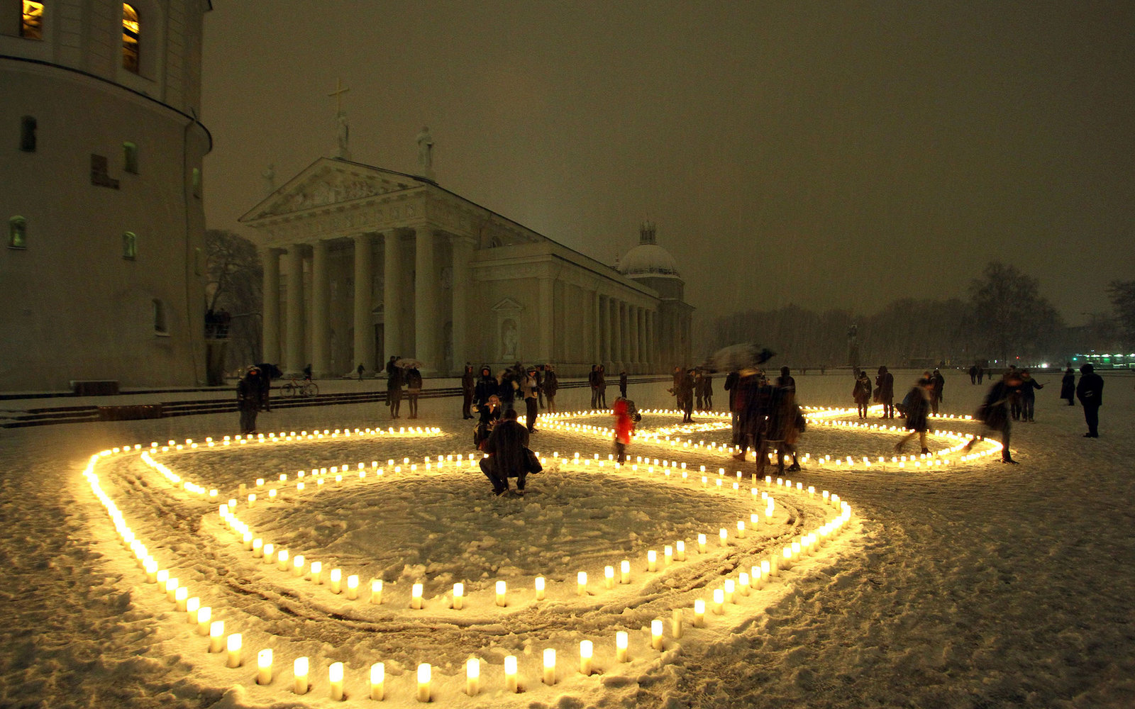 People attend a candle light vigil at the Vilnius Cathedral as it stands unlit during Earth Hour in Vilnius on March 19, 2016.Lights went off in thousands of cities and towns across the world for the annual Earth Hour campaign, aiming to call for action