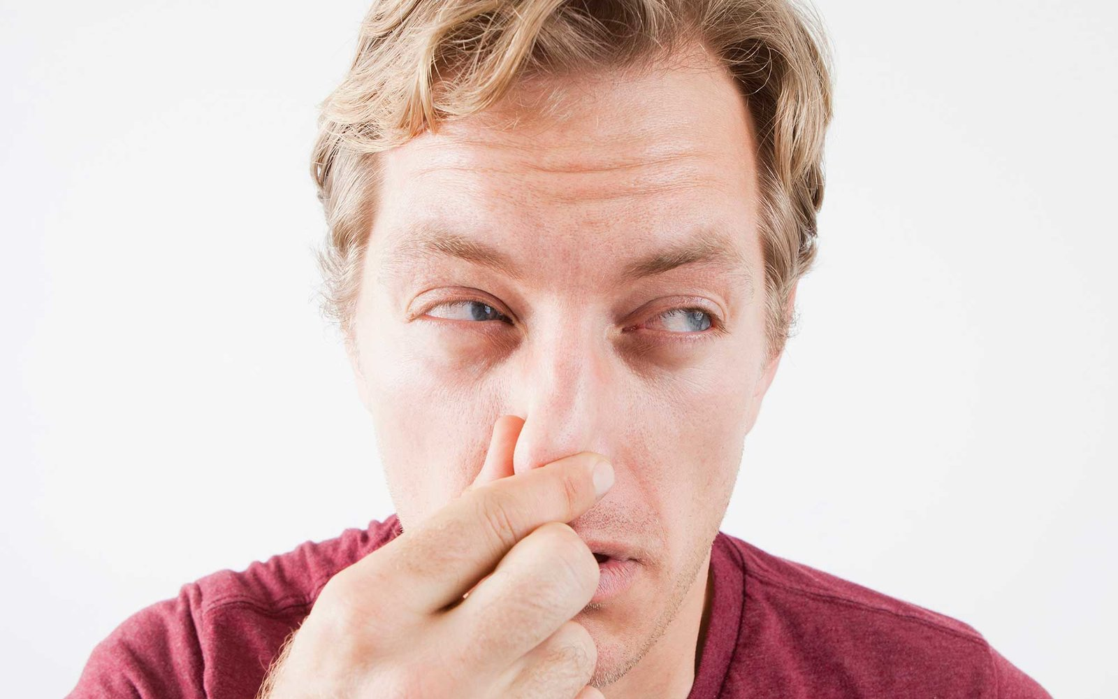 Studio Shot of mid adult man covering nose against unpleasant smell