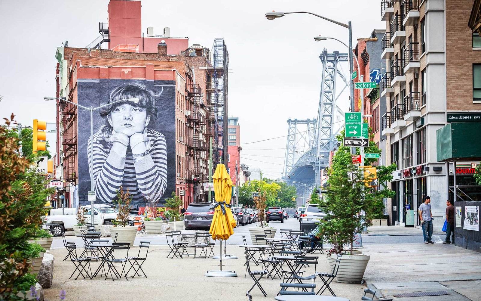 Streetscape in Williamsburg along Broadway with empty chairs on hazy day. Williamsburg bridge is visible in the background.