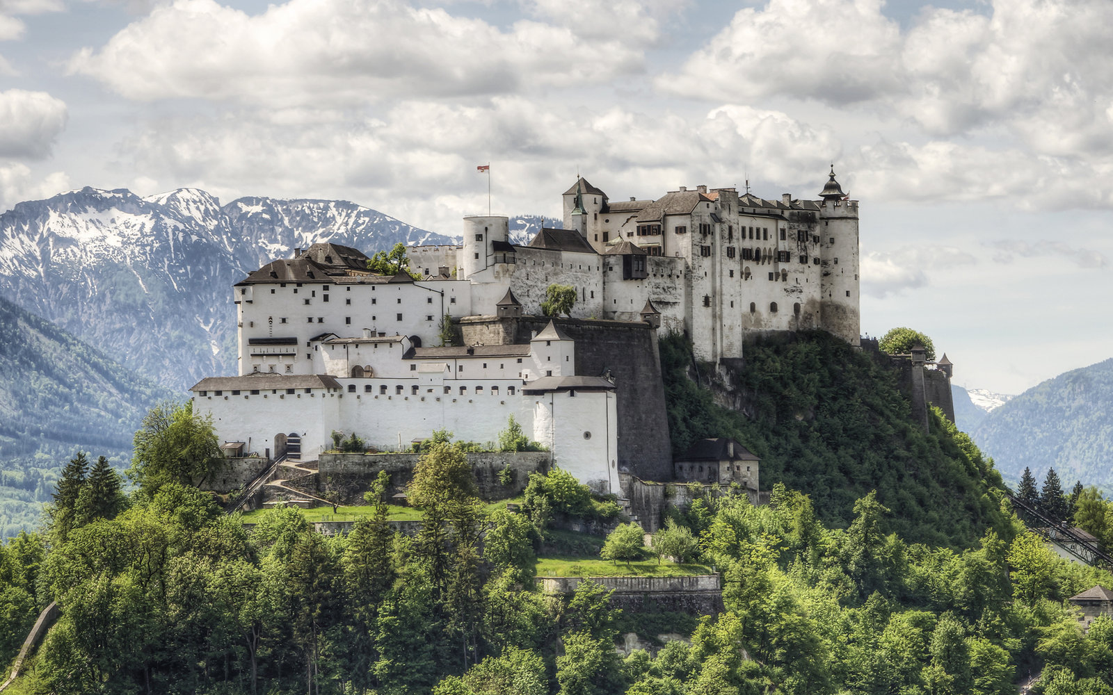 Salzburg, Austria: The Hohensalzburg Fortress in Salzburg Austria with Alps range rising in the distance. Built over several hundred years (from the 11th to 16th centures), it is one of the largest medieval castles in Europe with a length of 250 m (820 ft
