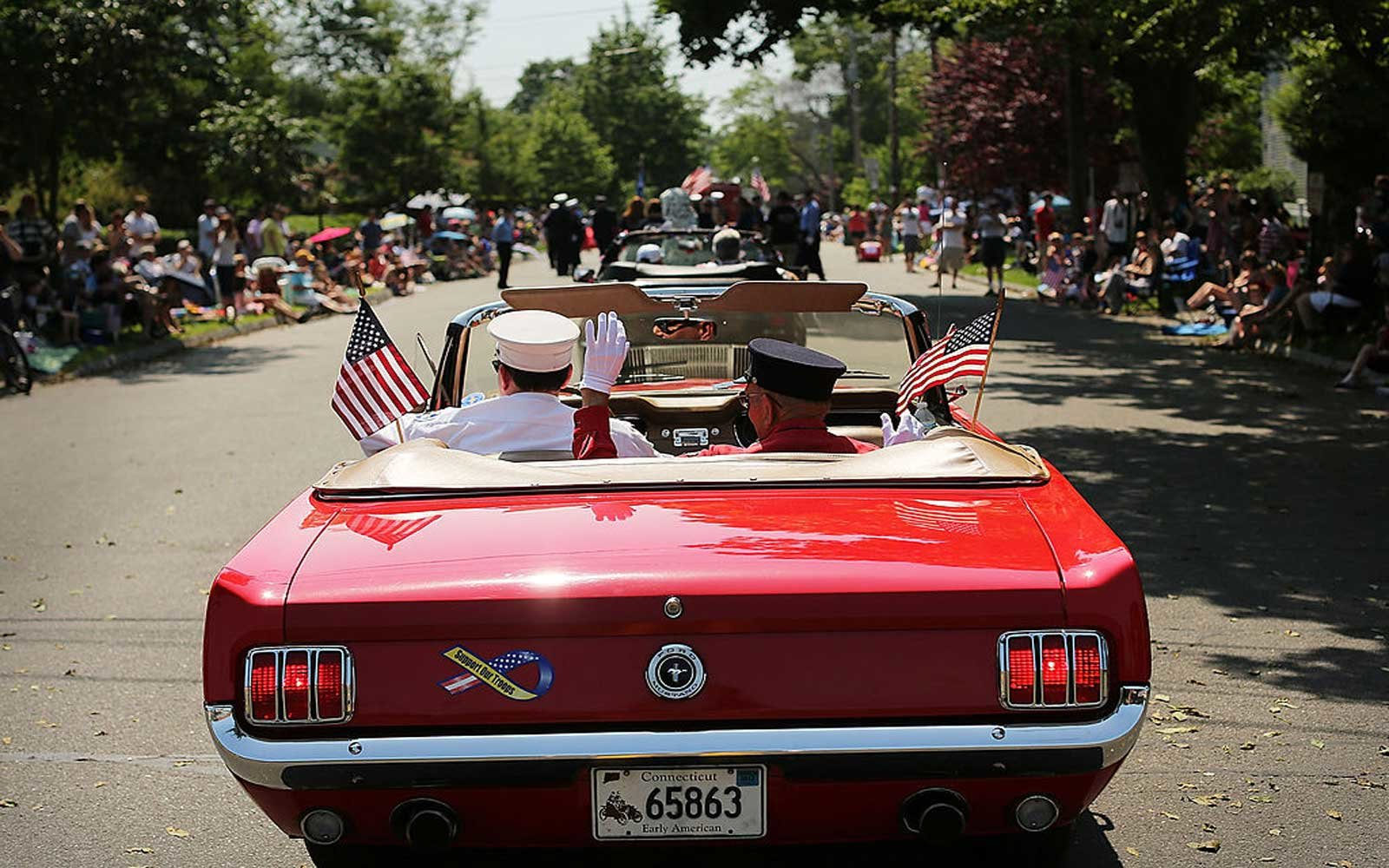 FAIRFIELD, CT - MAY 28:  Two firefighters ride in a convertible during the annual Memorial Day Parade on May 28, 2012 in Fairfield, Connecticut. Across America towns and cities will be celebrating veterans of the United States Armed Forces and the sacrifi