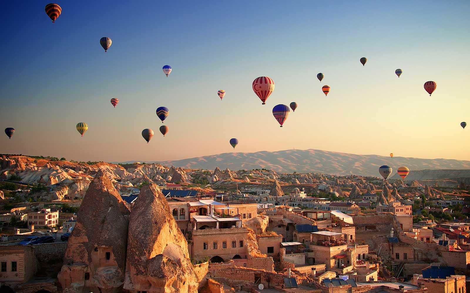 Sunrise in Cappadocia, Turkey, with balloons and typical fairy chimney.