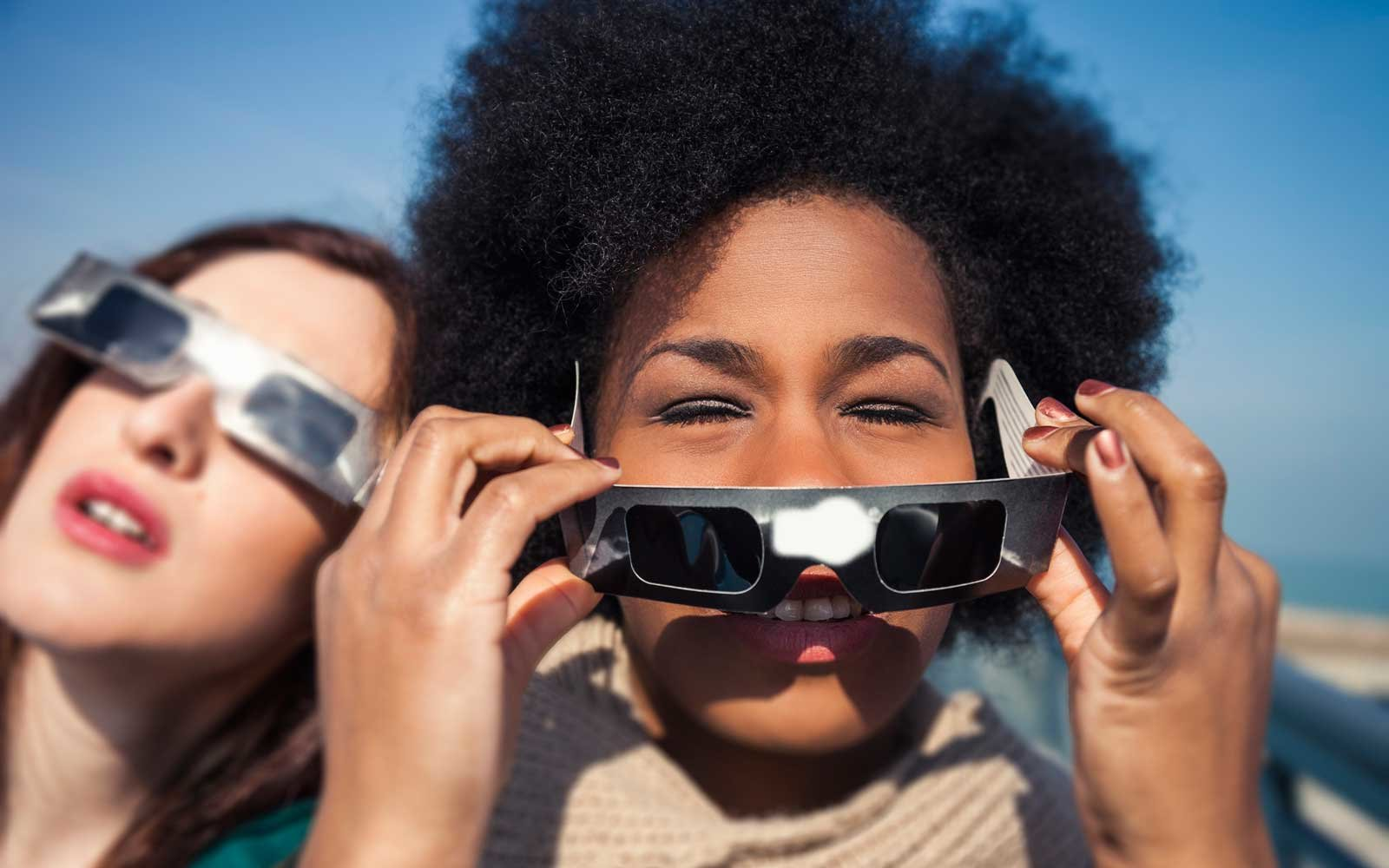 Group of female friends have fun together during a solar eclipse event.