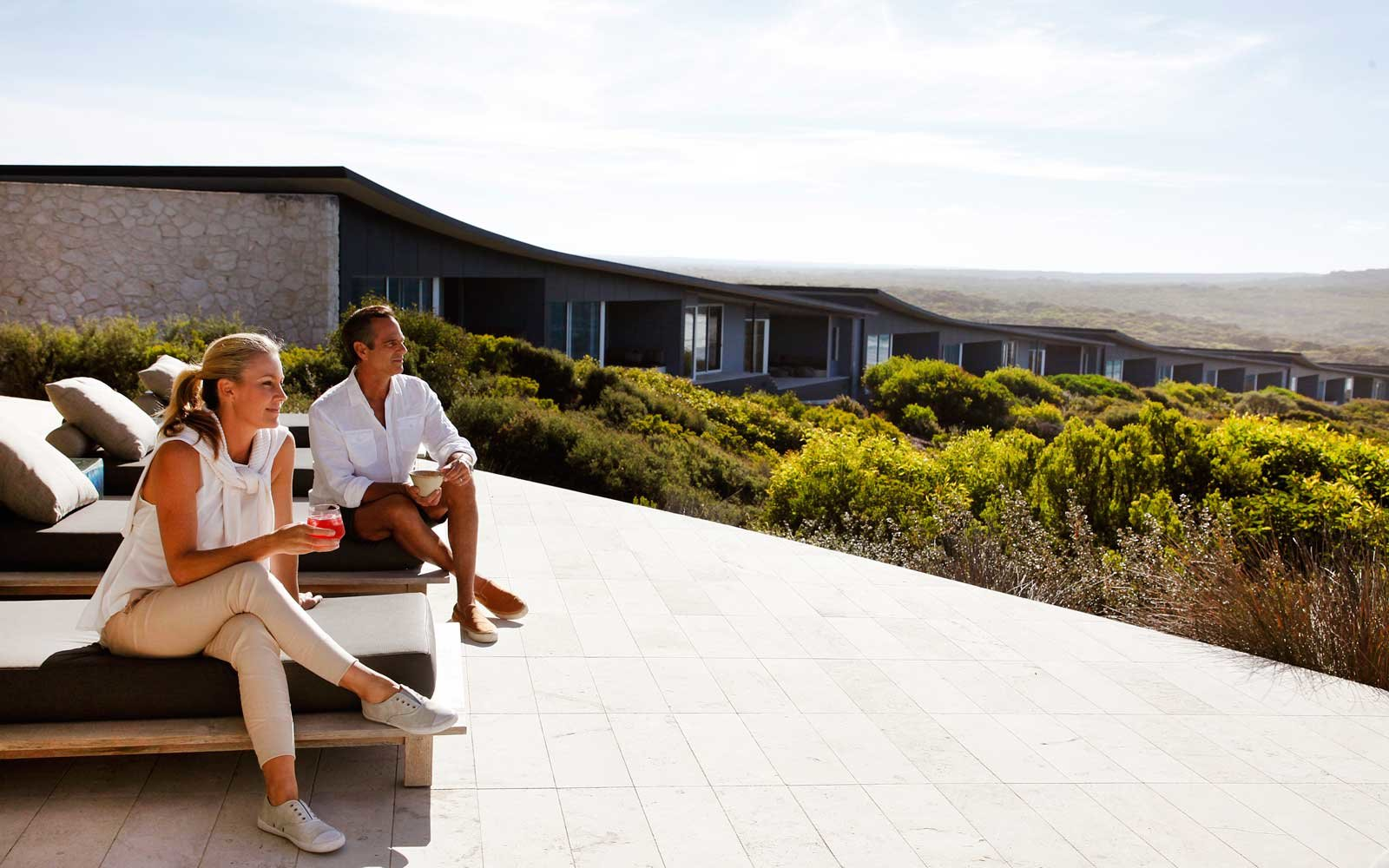 Couple enjoying drinks on the terrace of Southern Ocean Lodge, in Australia