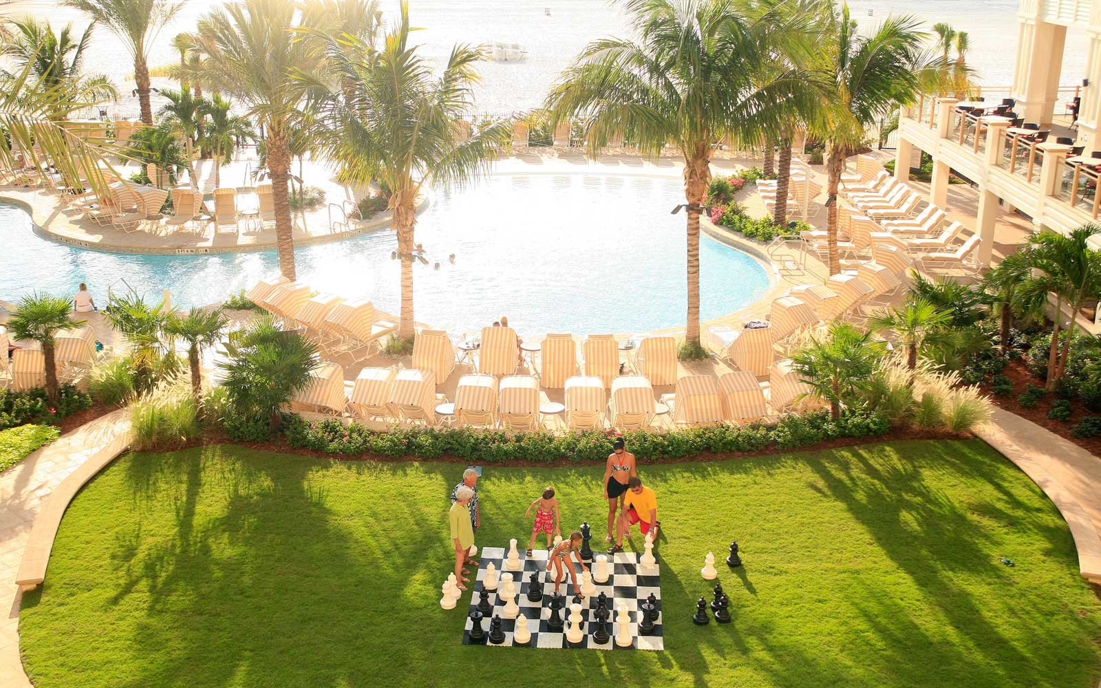 Family playing chess by the pool at the Sandpearl Resort in Clearwater Beach, Florida